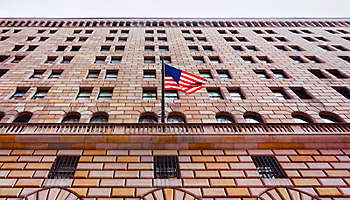 looking-upward-government-building-with-american-flag