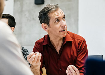 Mature Man Speaking in Meeting